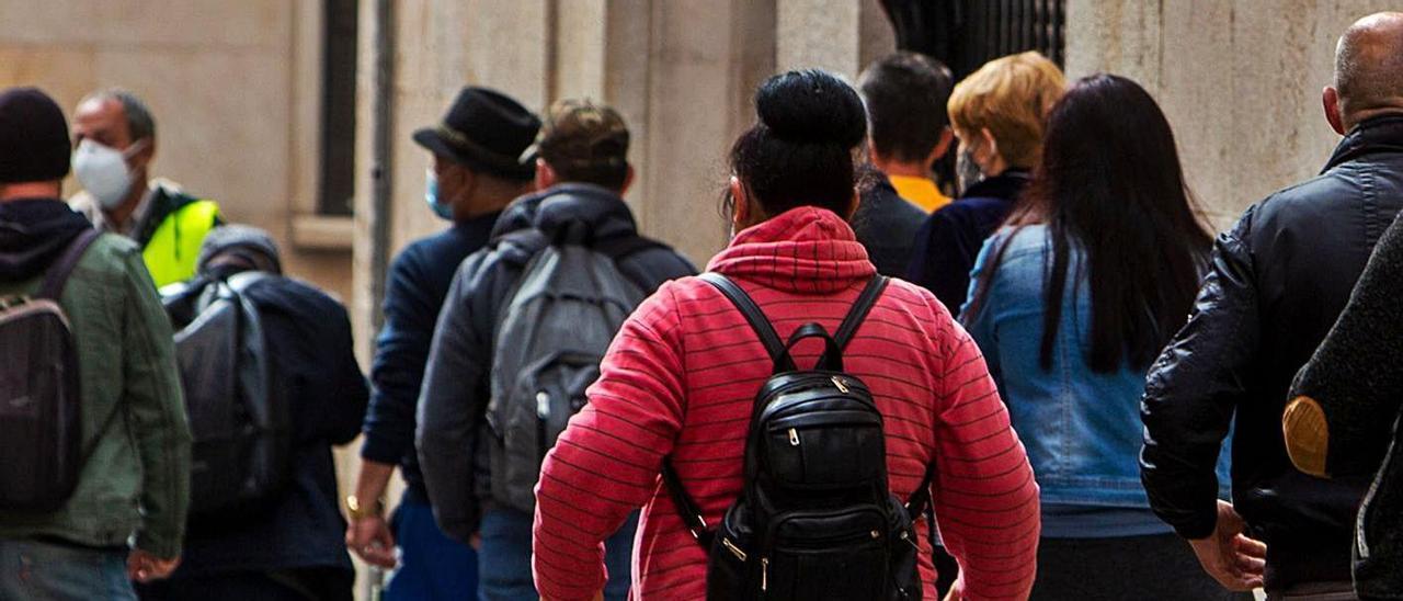 Personas esperando asistencia en Cáritas en el centro de Alicante, a principios de este mes.