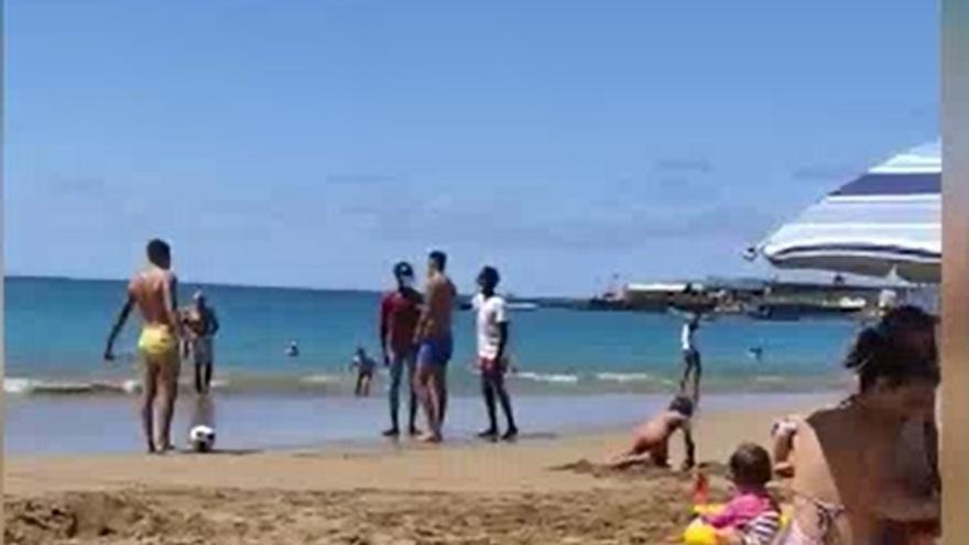 Dos jóvenes canarios comparten playa y balón con dos migrantes