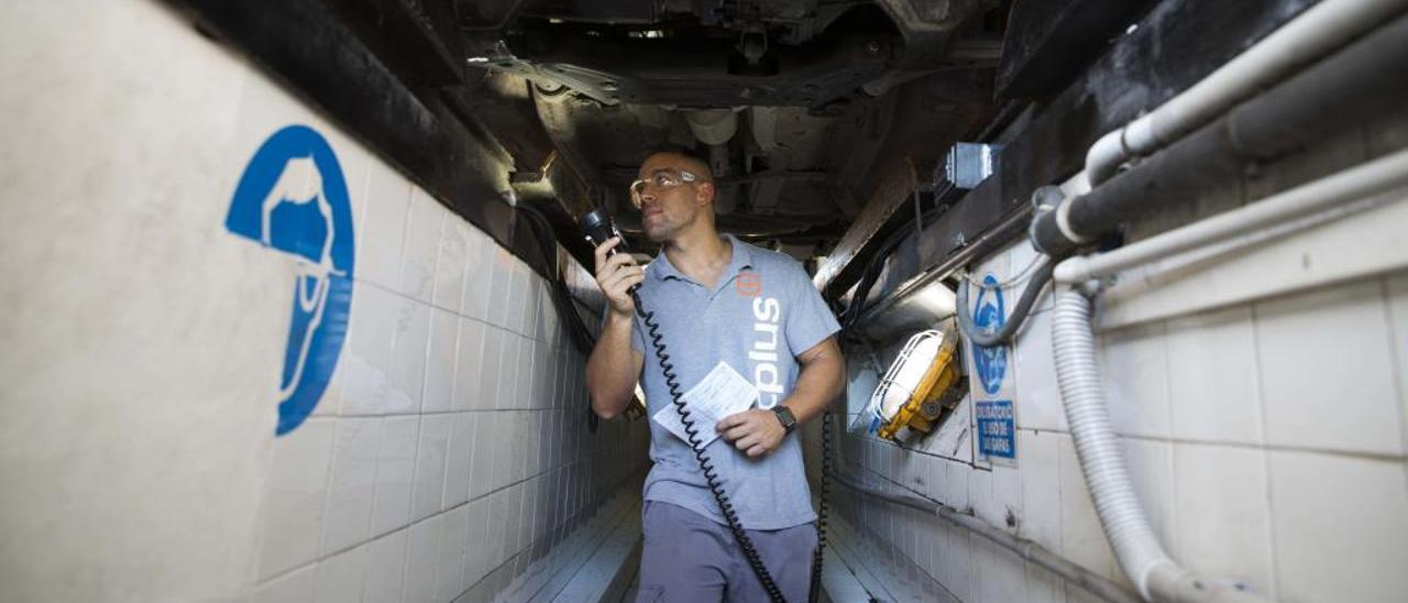 Un operario de la Inspección Técnica de Vehículos de Alicante examina los bajos de un coche en unos controles de seguridad cada vez más estrictos.
