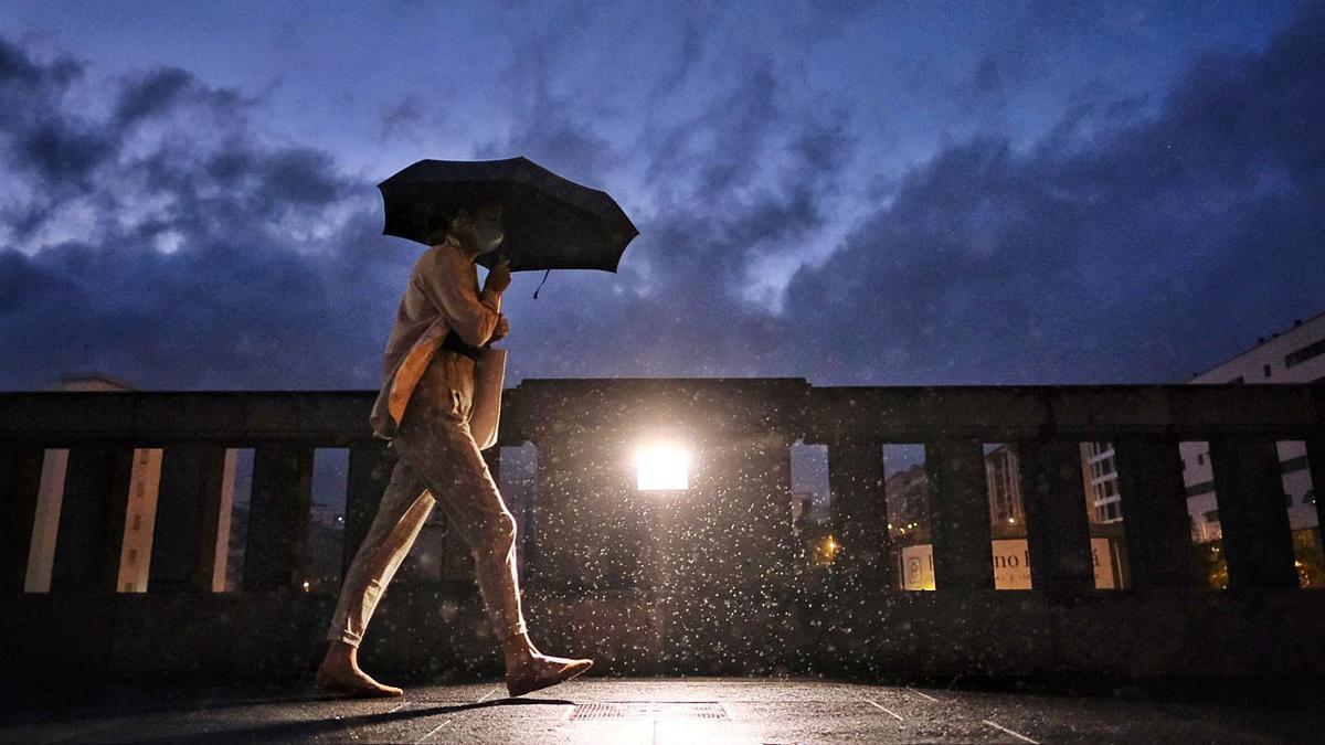 Una persona transita por un puente de la capital tinerfeña bajo la lluvia | | ANDRÉS GUTIÉRREZ