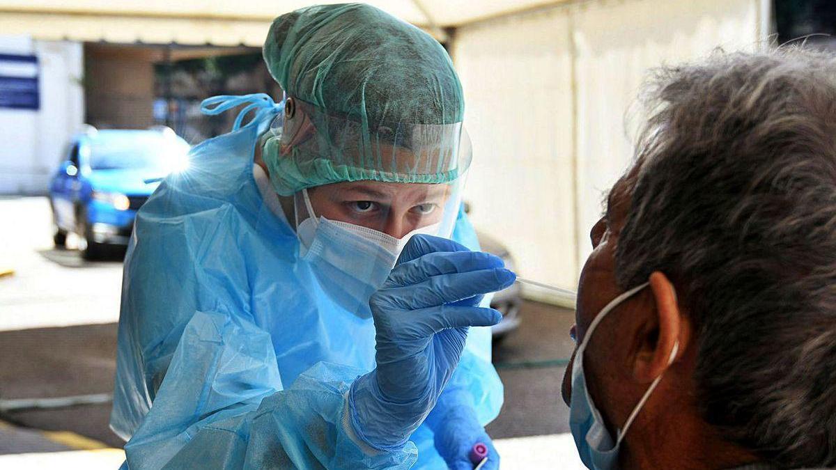 Una profesional sanitaria realizando una PCR a un paciente en el Hospital Provincial.