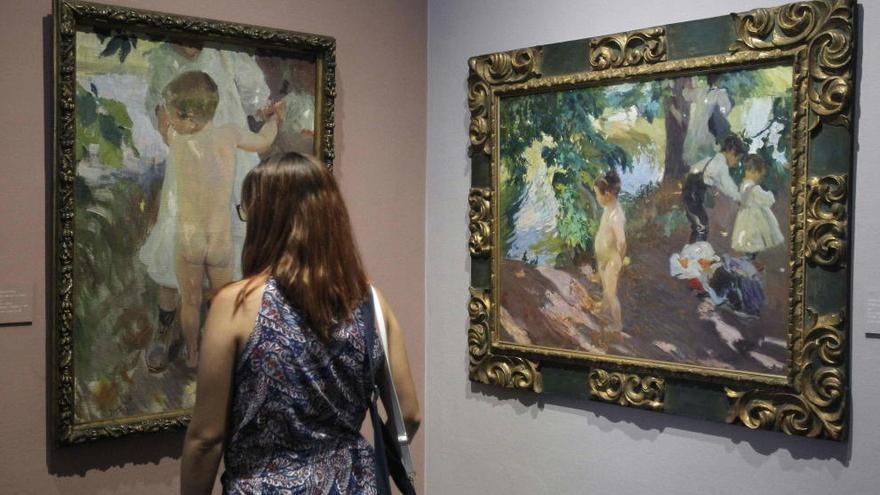 Una mujer observa los cuadros 'El niño de la granja' y 'El baño de la granja'