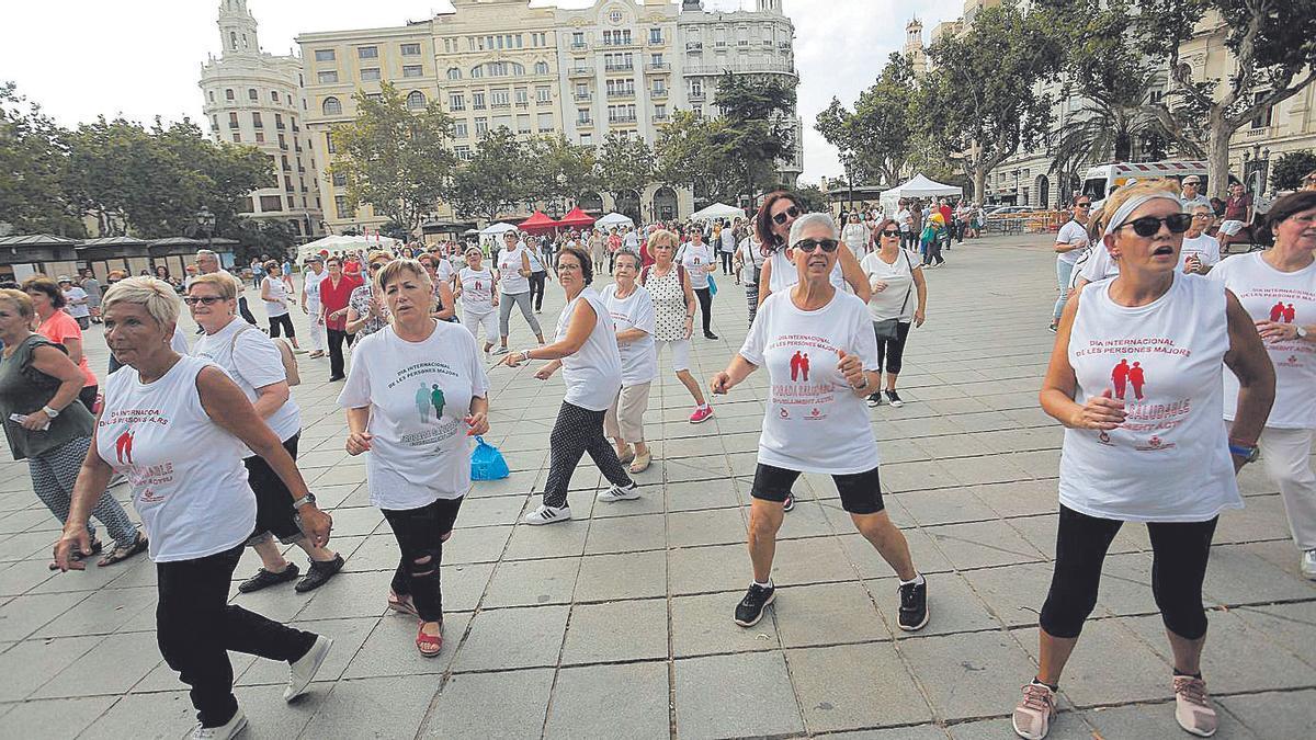 Una actividad física colectiva en la explanada de la Plaza del Ayuntamiento de València.
