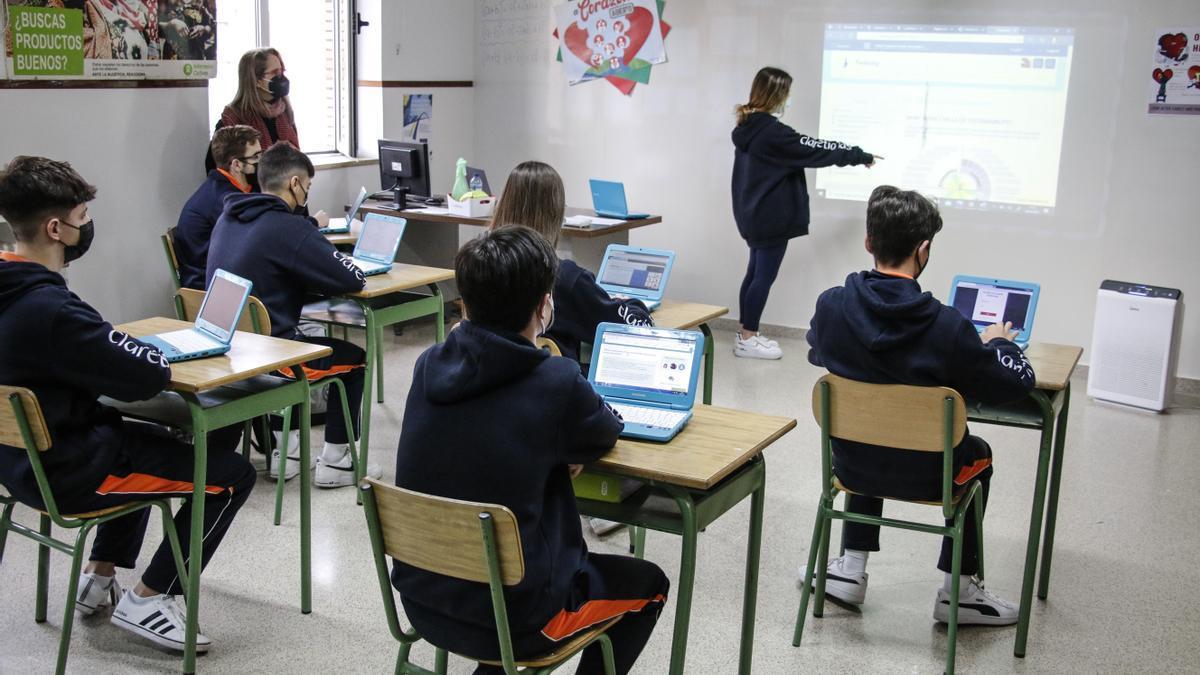 Un grupo de niños, con sus ordenadores en un aula