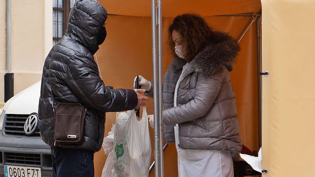 Una empleada de Cáritas entrega la ración diaria de alimentos a un joven.