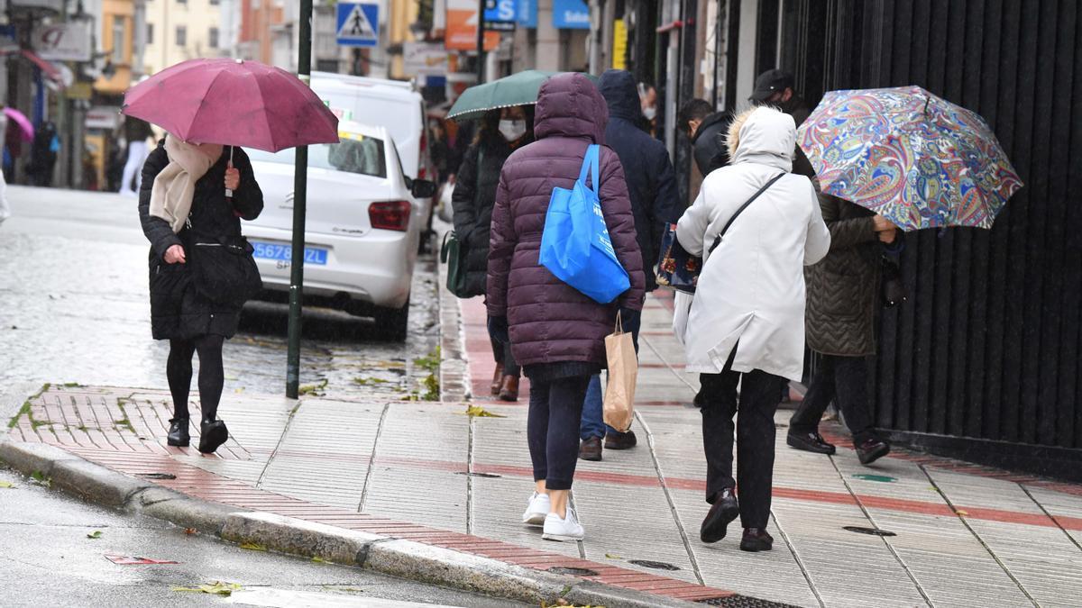 Varias personas con paraguas en A Coruña.