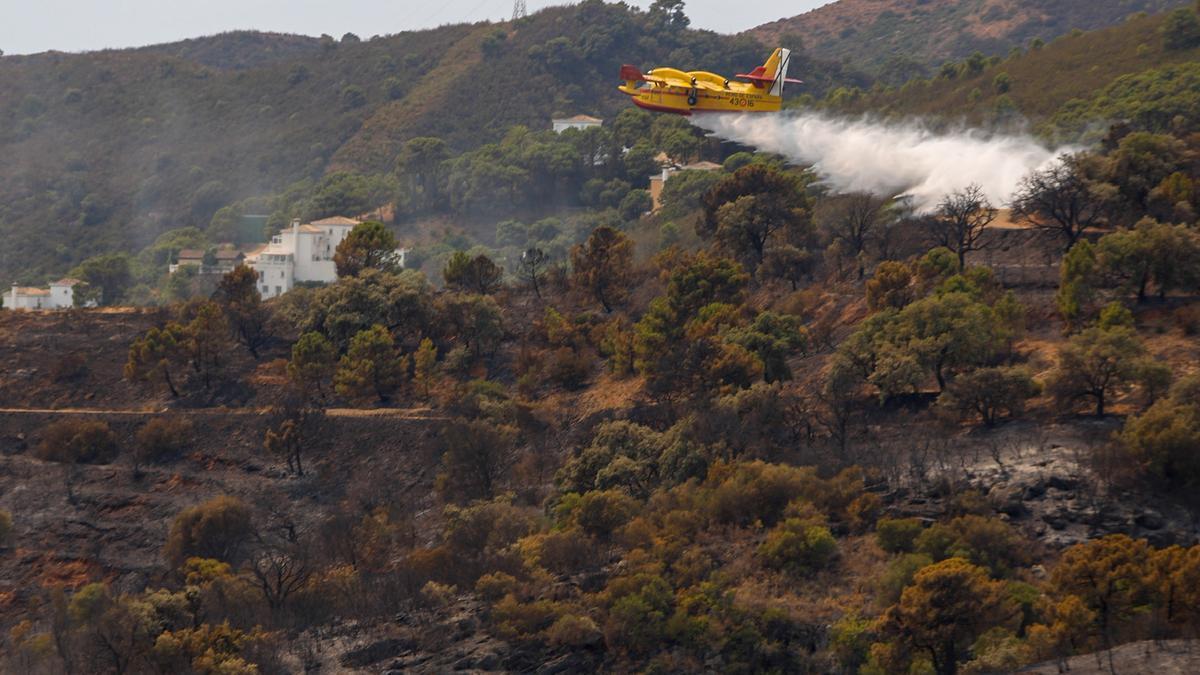 Un avión actúa en los parajes calcinados por el incendio en Sierra Bermeja.