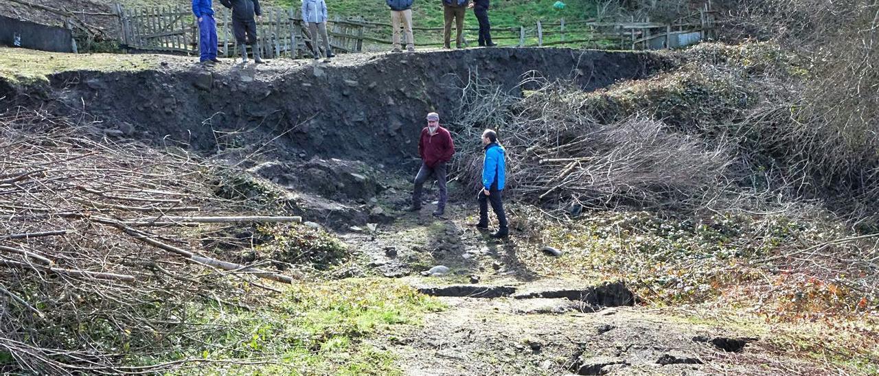 Vecinos denunciando la presencia de agujeros en  la zona de acceso a La Carisa.