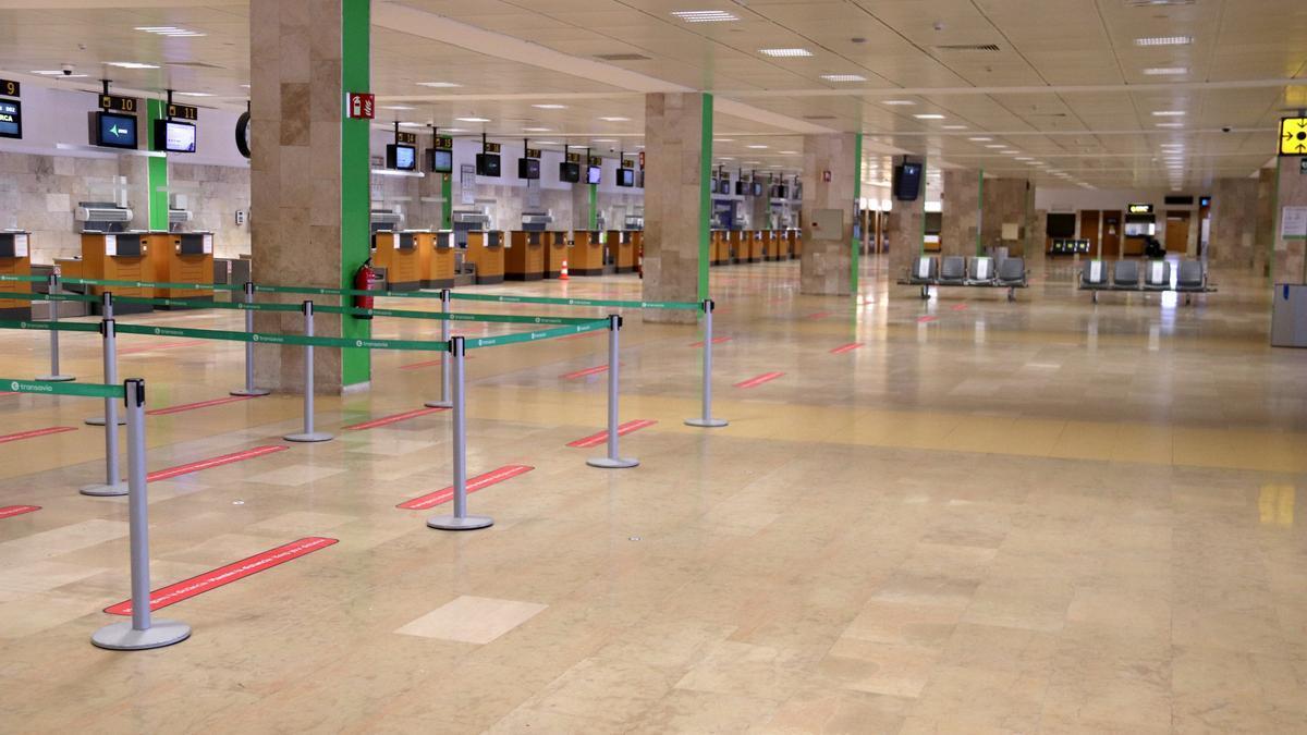 Pla obert dels taulells de facturació de l'aeroport de Girona completament buits amb les línies de distància entre passatgers marcades al terra el 28 de maig de 2021. (Horitzontal)