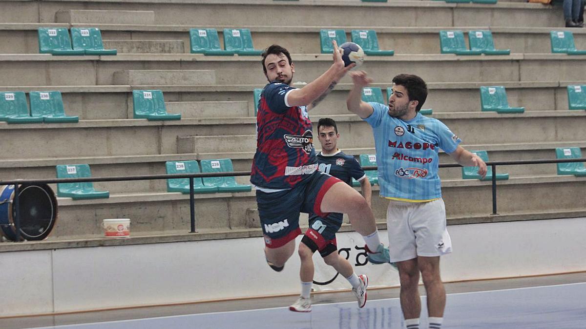 Martín Gayo lanza a puerta ante la defensa de un jugador del Seis do Nadal. |  // SANTOS ÁLVAREZ