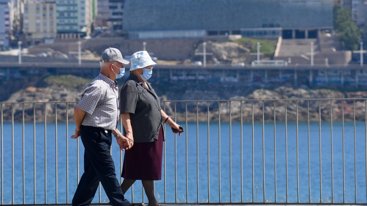 Una pareja camina por A Coruña con mascarilla.