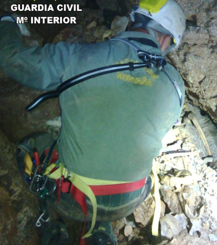 Un agente del GREIM junto a los restos hallados en la cueva de Tales.