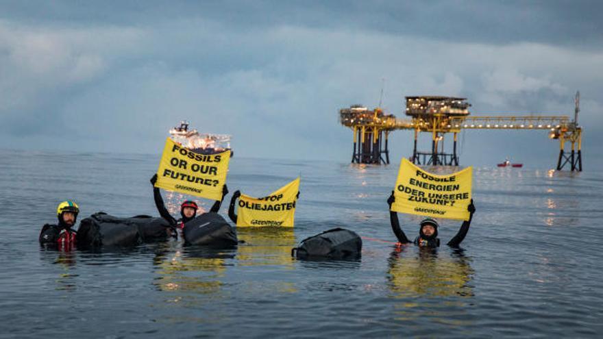 Miembros de Greenpeace nadan hasta una plataforma petrolífera en el mar del Norte