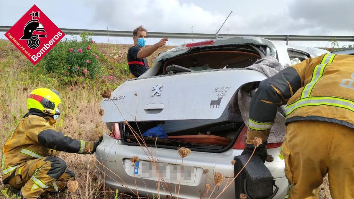 Los bomberos revisan el vehículo, que ha dado varias vueltas de campana