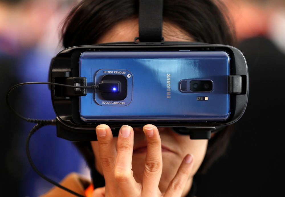 A woman tries out augmented reality glasses with ...