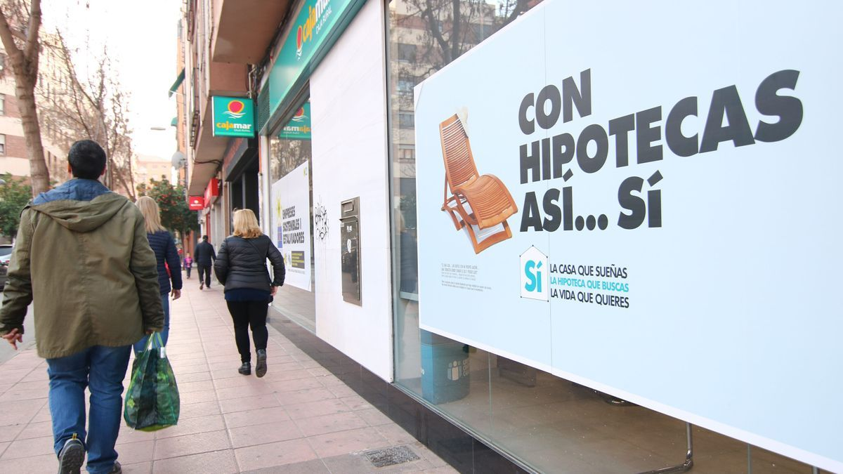 Varias personas pasan por una calle junto a los carteles en los que una entidad bancaria promociona sus créditos hipotecarios.