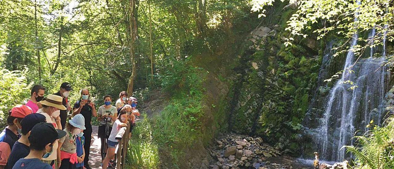 Visitantes durante una ruta teatralizada por la cascada de Xurbeo el pasado verano.