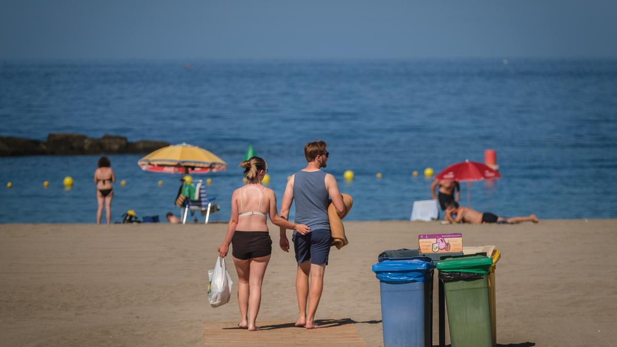 Una pareja de turistas pasea por una playa del Archipiélago