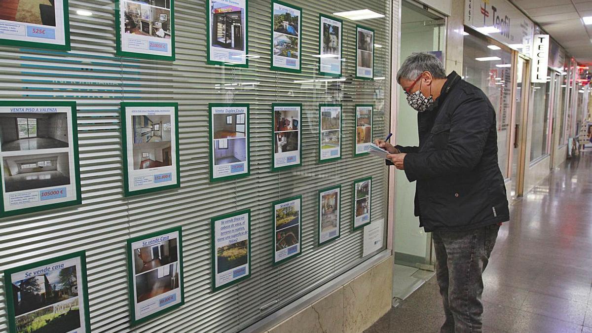 Un hombre observa las ofertas de pisos en una inmobiliaria. |   // IÑAKI OSORIO
