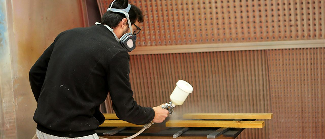 Un trabajador barniza unas placas de madera.