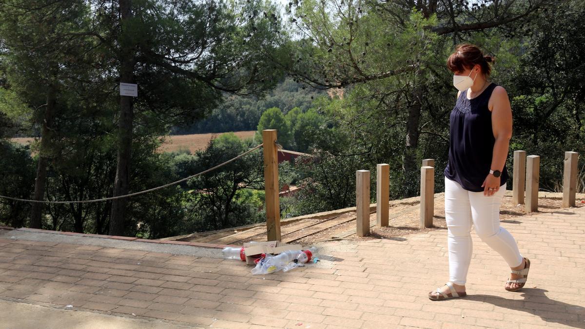 L'alcaldessa de Mont-ras mirant les deixalles del botellot d'aquesta matinada a la urbanització Can Burjats aquest 14 d'agost del 2021 (Horitzontal)