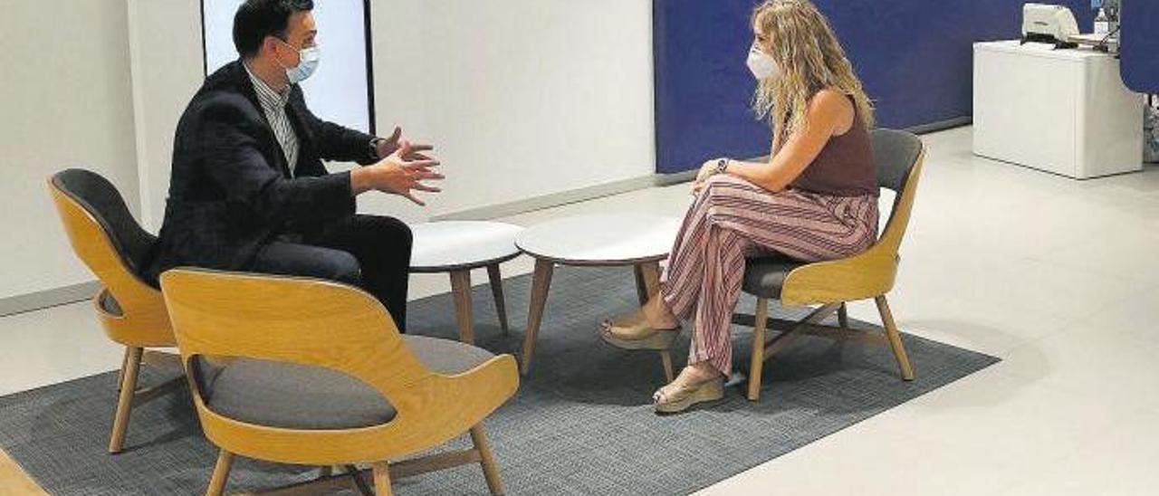 Una clienta, con un asesor financiero en una sucursal española.