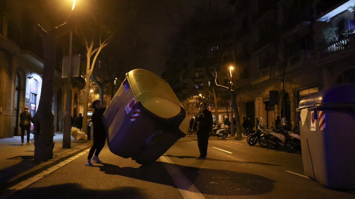 Manifestantes mueven un contenedor en una calle de Barcelona.