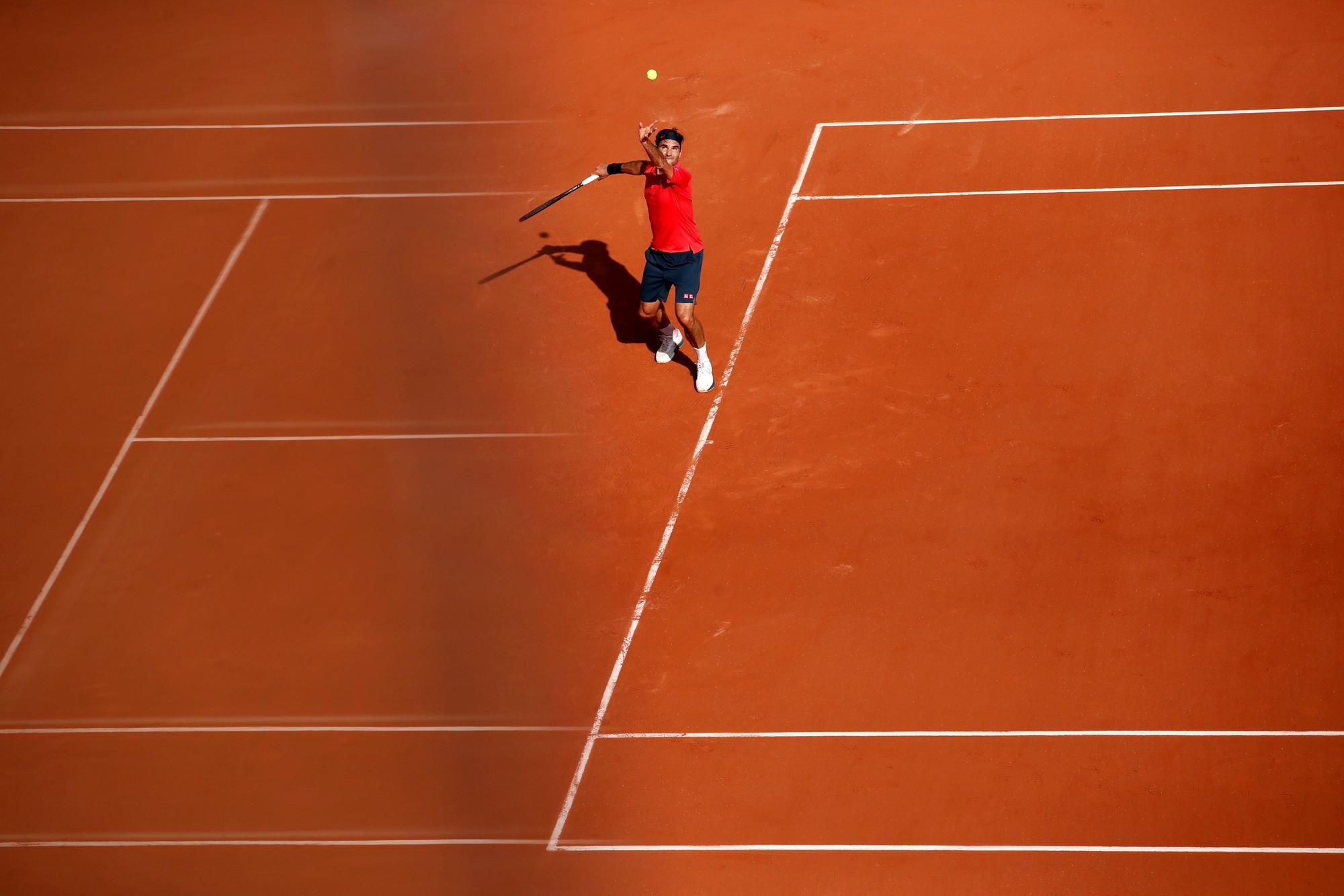 Roger Federer realiza un saque en su debut en la arcilla parisina de Roland Garros