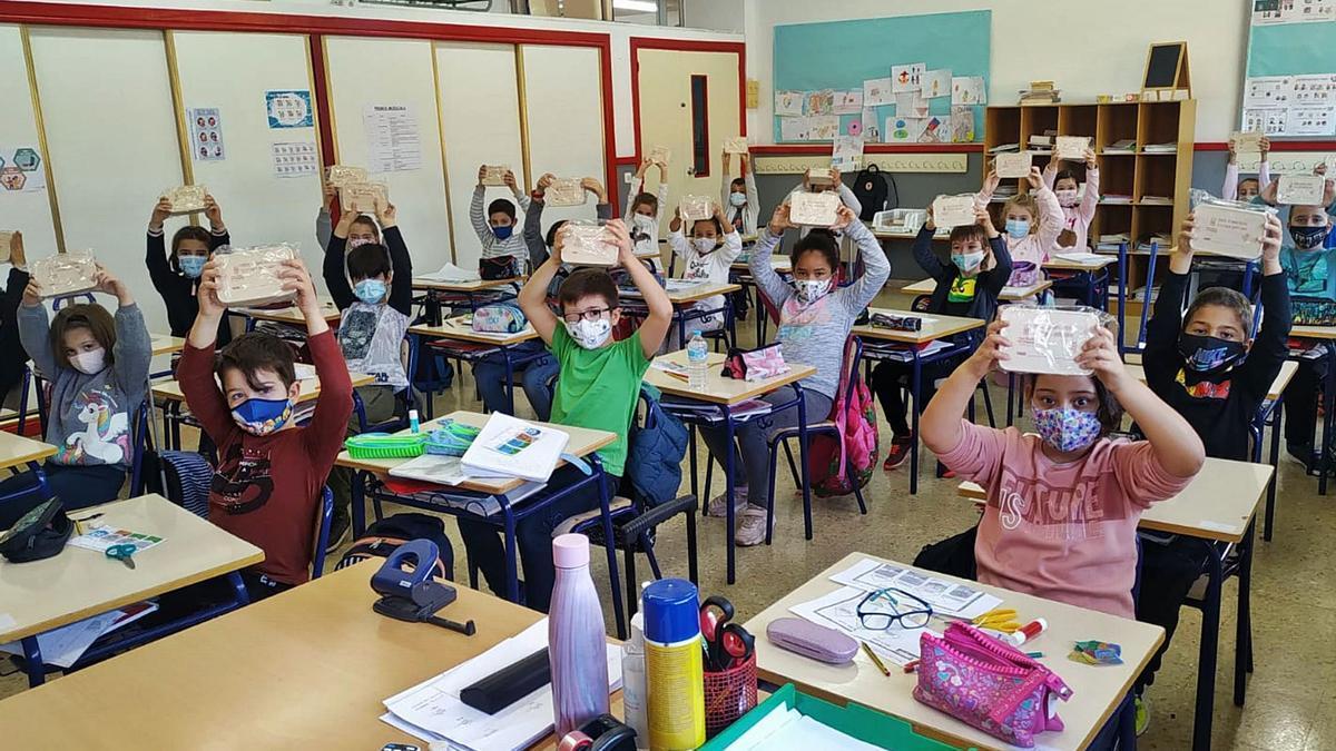 Una clase de tercero de primaria en San Vicente enseña las tarteras de bambú que regala Medio Ambiente, aunque están envueltas en plástico.  | INFORMACIÓN