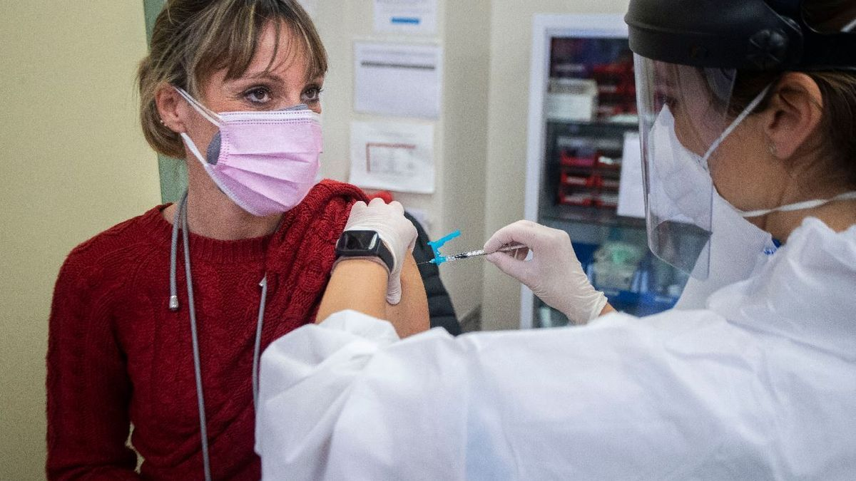 Una enfermera vacuna contra la covid a una mujer.