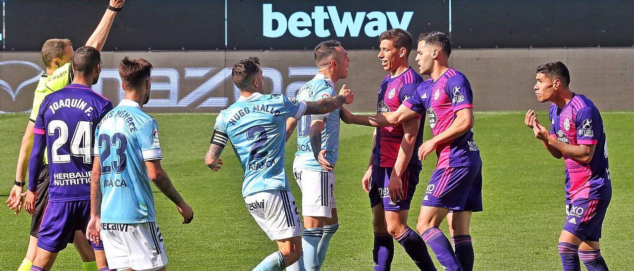 El árbitro amonesta a Lucas Olaza, a la derecha, tras derribar a Santi Mina al borde del área del Valladolid. |  // MARTA G. BREA