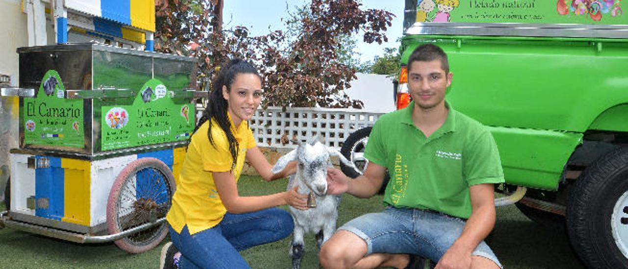 Dos de los empleados de El Canario con la cabra 'Lucía' en la heladería en Telde.