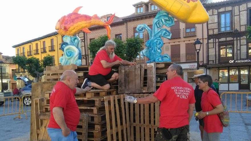 Responsables y socios del colectivo trabajan en el montaje de la hoguera de San Juan.