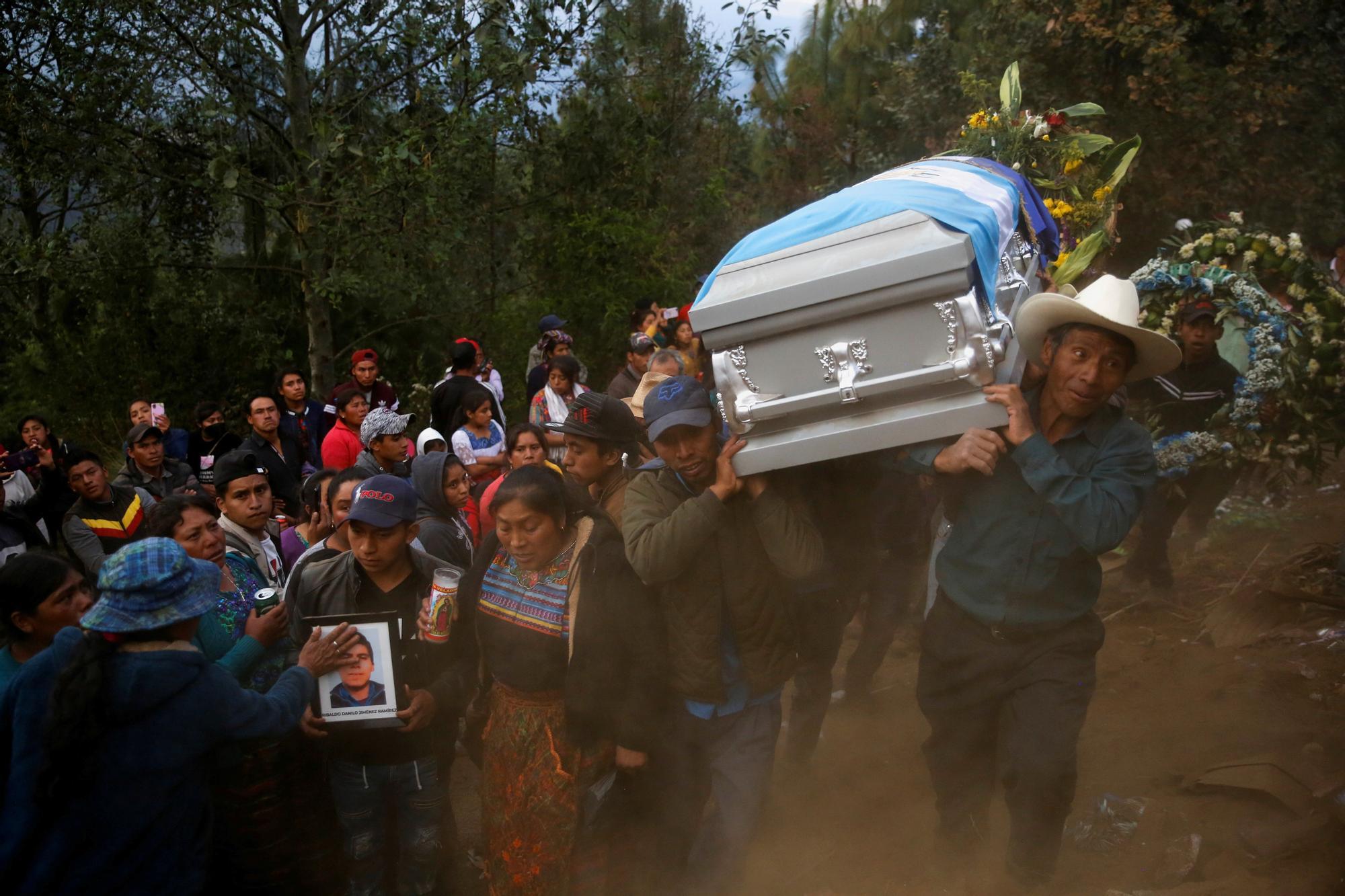 Hombre cargan con el féretro de un compatriota fallecido en México