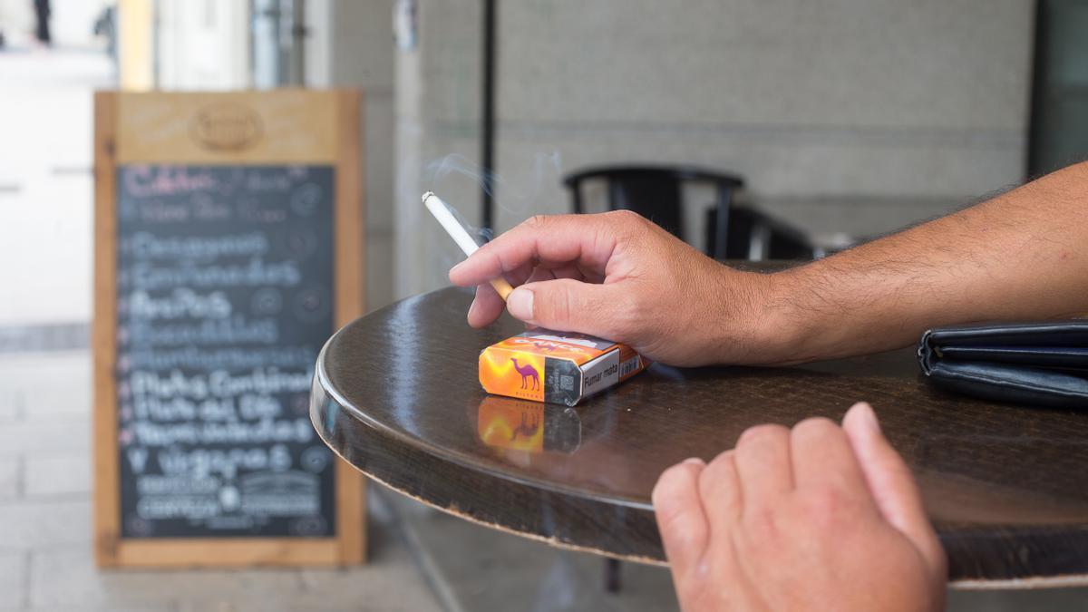 Un home fumant en una terrassa d'un bar