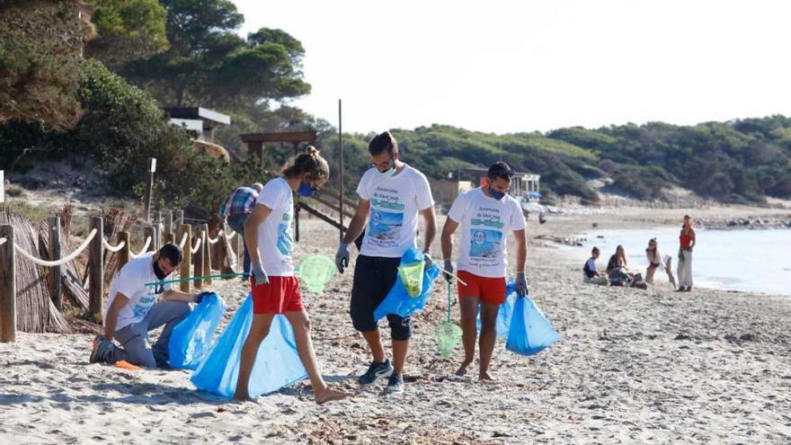 Los socorristas de Sant Josep limpian la playa de ses Salines en su último día de trabajo
