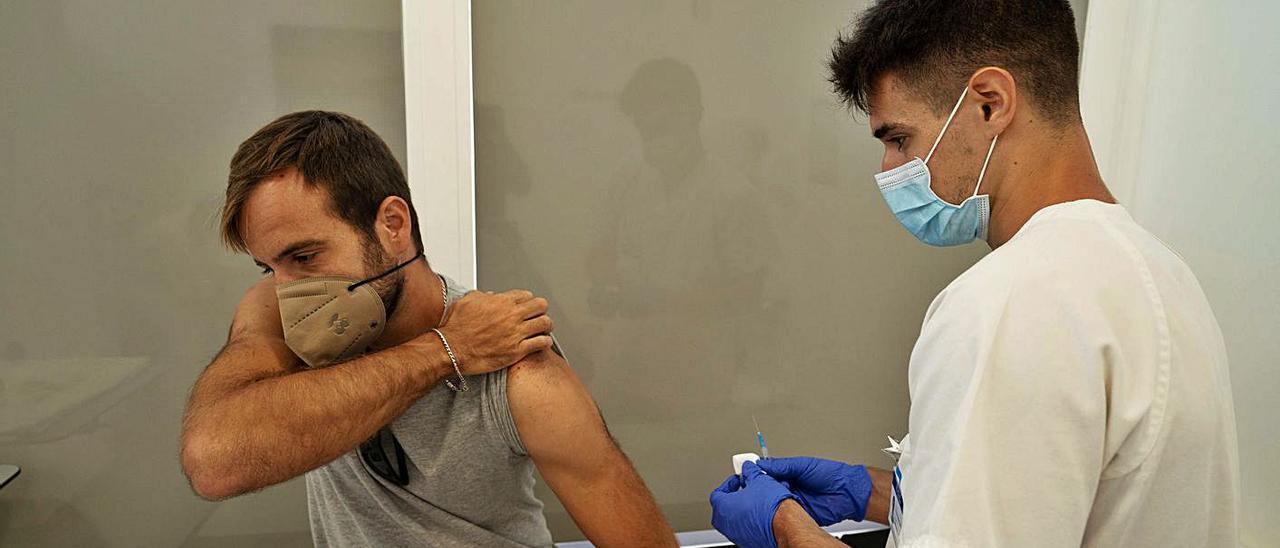Un sanitario se dispone a administrar la vacuna a un usuario en Vila Parc.