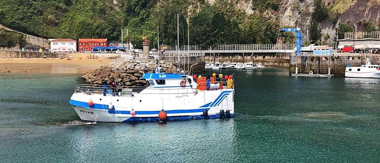 Una embarcación varada hace unos meses en el acceso a la zona de amarre del puerto de Lastres.   E. San Román
