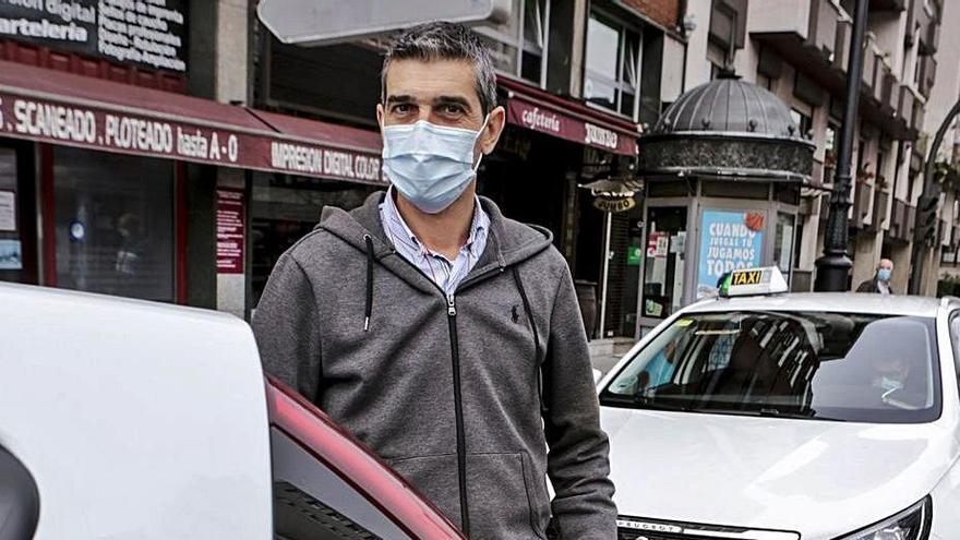 Miguel Feito, con su taxi con distintivo rojo, en la parada de Federico García Lorca. | Julián Rus