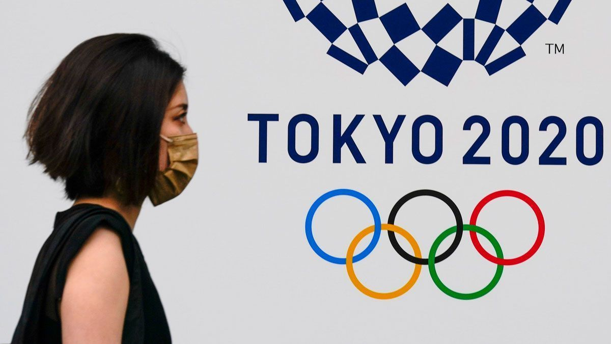 Una mujer pasa junto al emblema de los juegos olímpicos, en una calle de Tokio. /