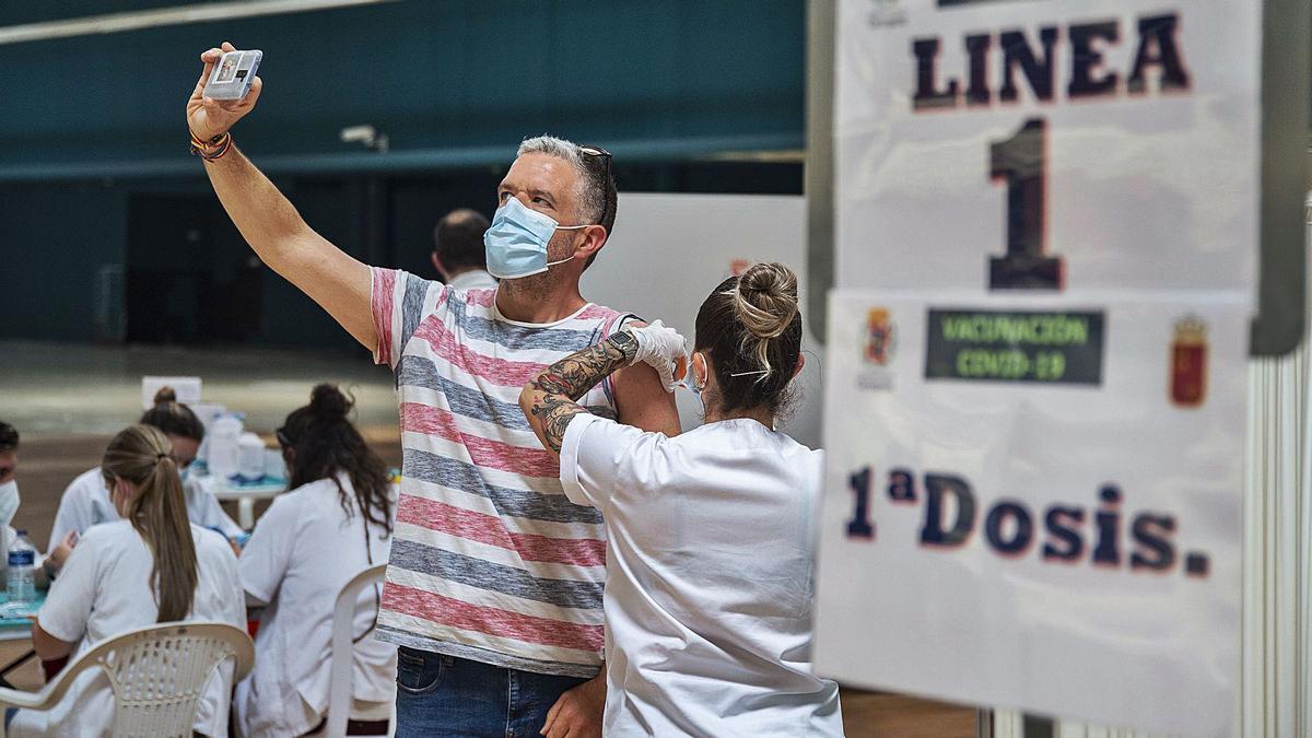 Una enfermera administra la vacuna contra el coronavirus a un usuario que aprovecha para inmortalizar el momento haciéndose un selfie, en Cartagena.   IVÁN URQUÍZAR