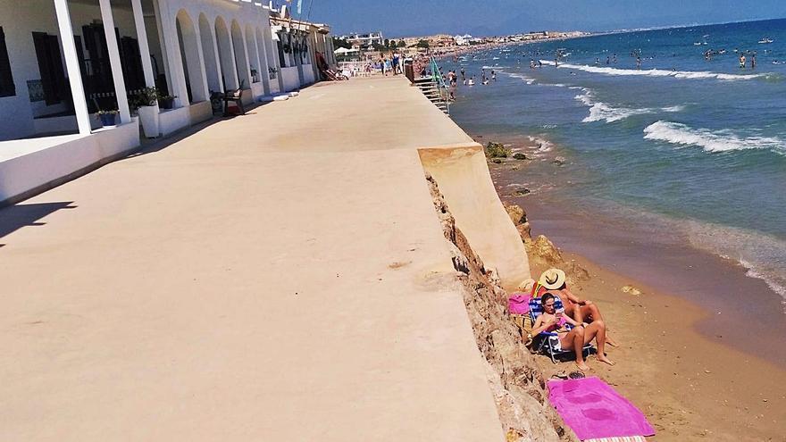 Los bañistas se meten en los resquicios de arena de la playa perdida de Dénia