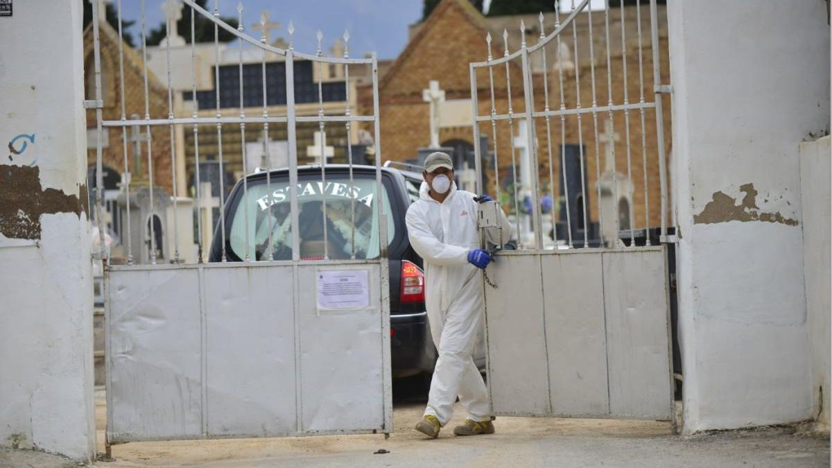 Una persona con un EPI cierra la puerta de un cementerio en Cartagena.