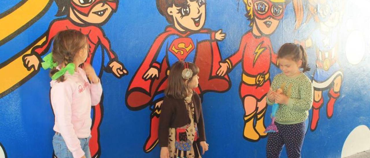 """Tres niñas eligiendo a su superheroína favorita junto al mural; a la derecha, el """"trenín"""", junto al mural completo, en Les Conserveres."""