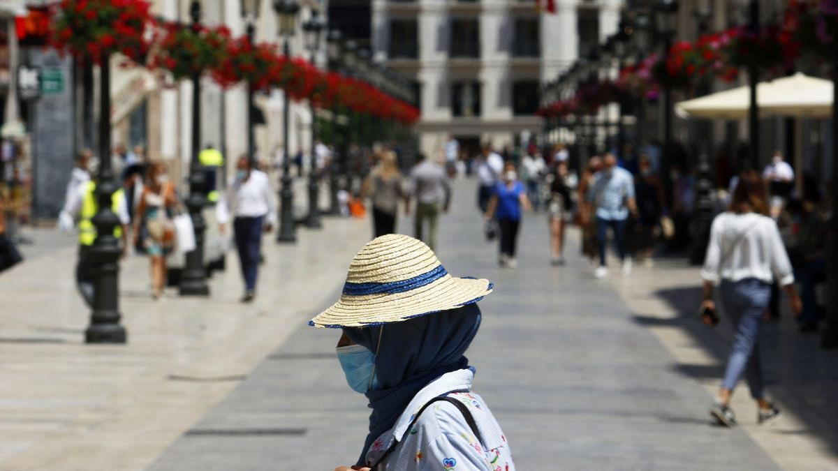 Viandantes con mascarillas en la calle Larios.