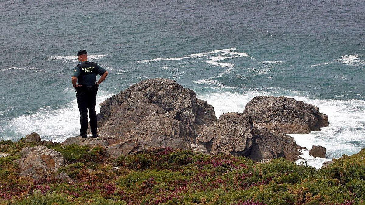Un agente de la Guardia Civil, en las inmediaciones del lugar en el que el pescador asturiano cayó al mar, ayer, en el litoral de Valdoviño (La Coruña), en los alrededores de la playa de El Baleo.