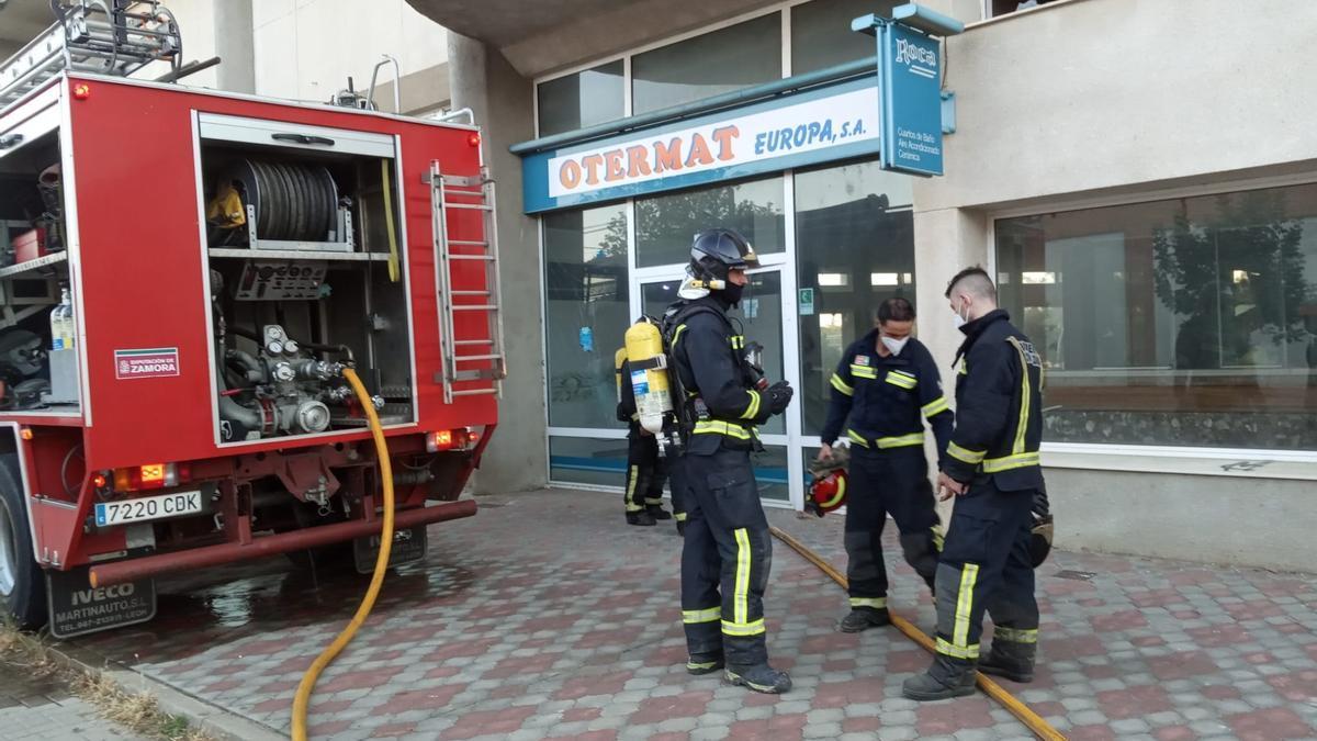 Los bomberos a las puertas del almacén donde sofocaron el incendio.
