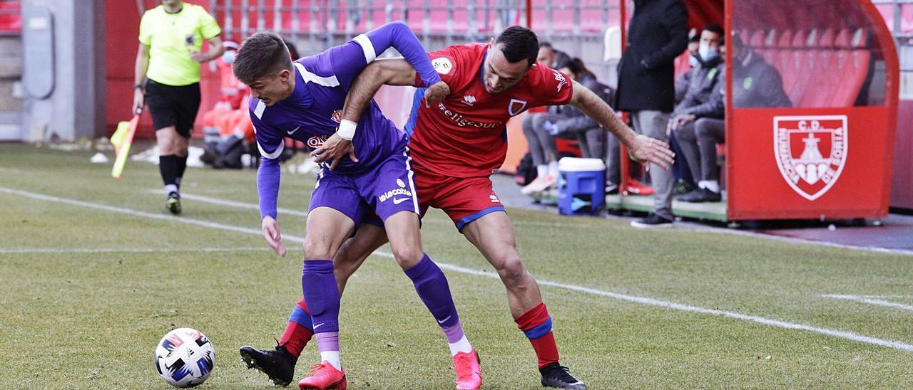 Trabanco disputa el balón con un jugador del Numancia. | Luis Ángel Tejedor / Heraldo de Soria