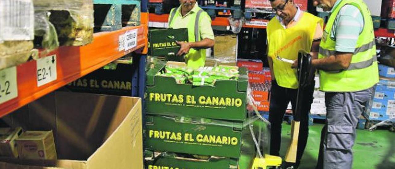 Un grupo de voluntarios coloca unas cajas de plátanos llegadas a los almacenes centrales del Banco de Alimentos en Mercalaspalmas.