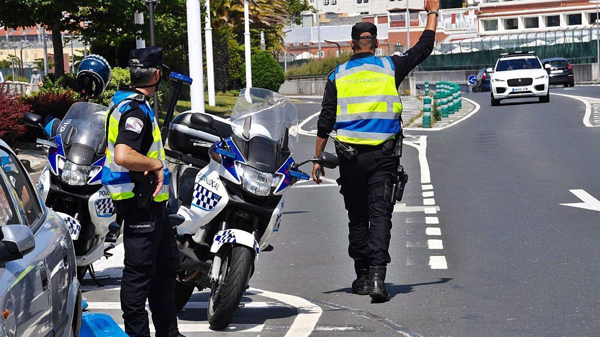 Dos policías locales ordenan a un conductor que detenga su coche en O Parrote. |   // CARLOS PARDELLAS